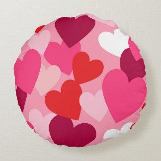 Diseño rosado, púrpura y blanco de los corazones cojín redondo