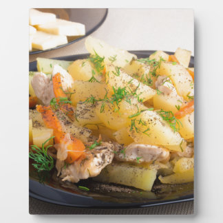 Dish of stewed potatoes with meat and spices plaque