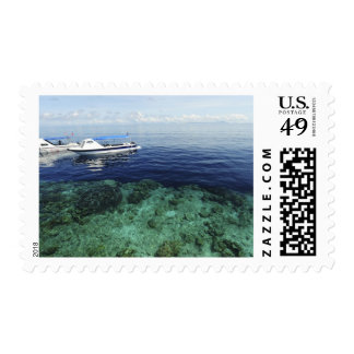 Diving boat arriving above sea and corals postage