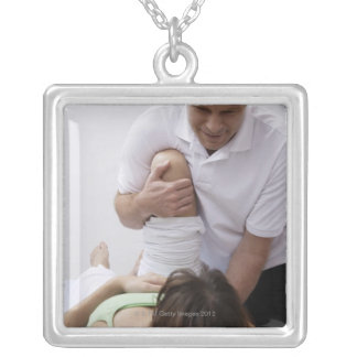 Doctor applying treatment to patient square pendant necklace