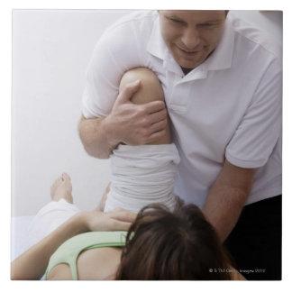 Doctor que aplica el tratamiento al paciente azulejo cuadrado grande