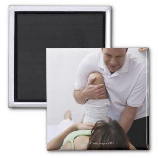 Doctor que aplica el tratamiento al paciente imanes para frigoríficos