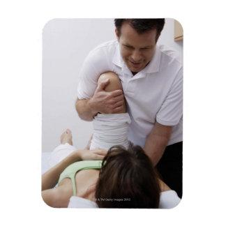 Doctor que aplica el tratamiento al paciente iman flexible