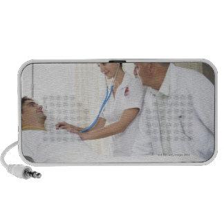 Doctor y enfermera que tienden al paciente laptop altavoz