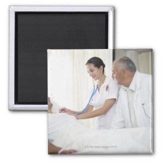 Doctor y enfermera que tienden al paciente imán cuadrado