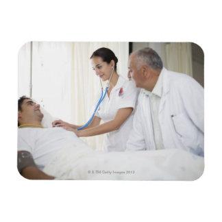 Doctor y enfermera que tienden al paciente imanes rectangulares