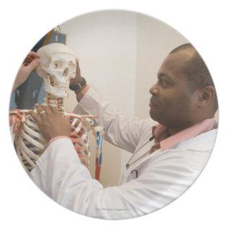 Doctores del estudiante que estudian la anatomía e plato de comida