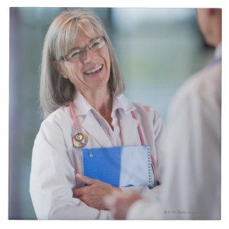 Doctores que hablan junto en vestíbulo del azulejo cuadrado grande