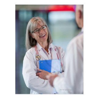 Doctors talking together in hospital hallway postcard
