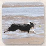 Dog chasing a ball at the beach beverage coaster