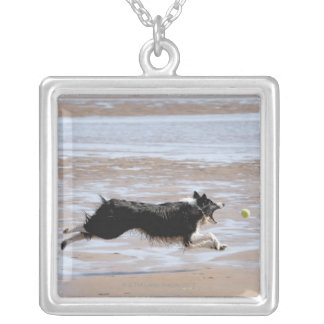 Dog chasing a ball at the beach silver plated necklace