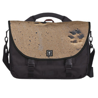 Dog paw prints on a sandy beach laptop bag
