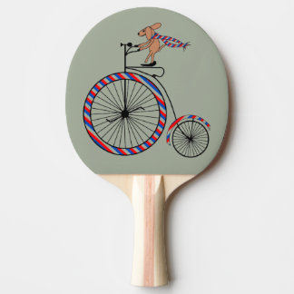 Dog Riding Old-Fashioned Bike on Ping Pong Paddle