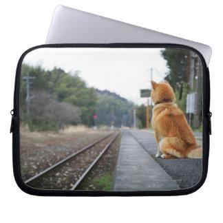 Dog sitting on train station laptop sleeve