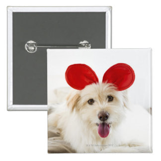 Dog wearing toy ears on bed pinback button