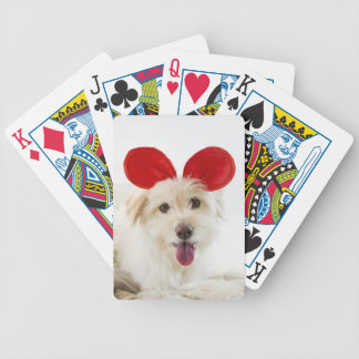 Dog wearing toy ears on bed deck of cards