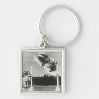 Dogs jumping over miniature high jump bar key chains