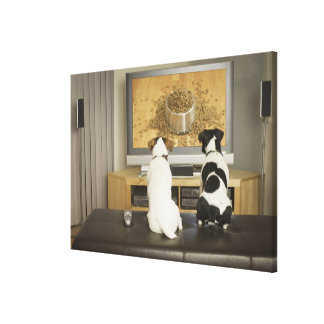 Dogs watching dog dish with food on TV Canvas Print