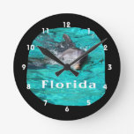 dolphin coming out of teal clear water florida wall clock