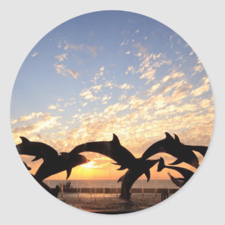 Dolphin's jumping from the water at sunset classic round sticker