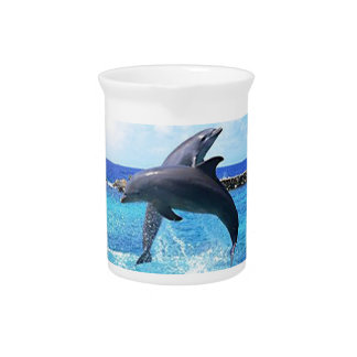 Dolphins playing in the ocean beverage pitcher