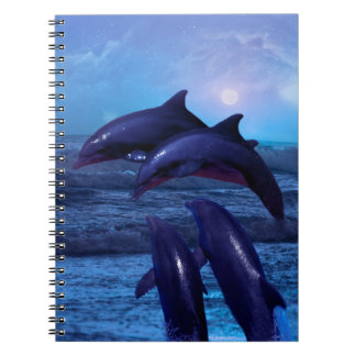 Dolphins playing in the ocean notebook