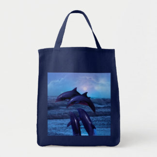 Dolphins playing in the ocean tote bag