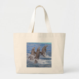 Dolphins standing out of the water large tote bag