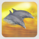 Dolphins surfing the waves square sticker