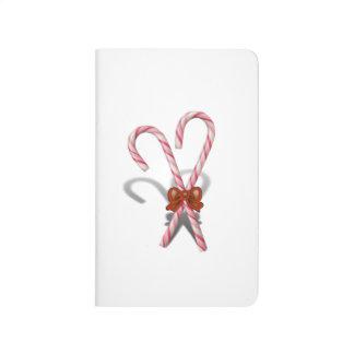Dos bastones de caramelo del navidad con la cinta cuaderno grapado