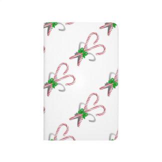 Dos bastones de caramelo del navidad con la cinta cuadernos
