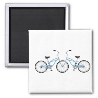 Dos bicicletas azules que entrelazan imán de frigorifico
