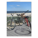 Dos bicis en orilla del jersey del paseo marítimo tarjeton