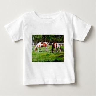Dos caballos de la pintura que pastan playera de bebé