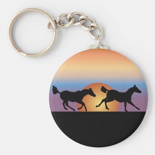 Dos caballos que corren contra una salida del sol llaveros