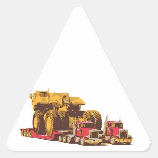 Dos camiones semi grandes que llevan un camión de pegatina triangular