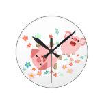 Dos cerdos lindos del dibujo animado en reloj de p