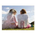 Dos chicas (7-9) vestidos como ángel y hada postal