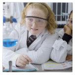 Dos chicas en capas del laboratorio del uniforme e azulejo cuadrado grande