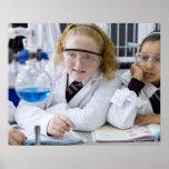Dos chicas en capas del laboratorio del uniforme e póster