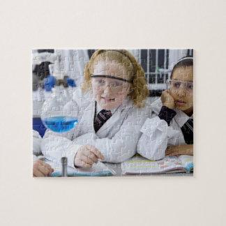 Dos chicas en capas del laboratorio del uniforme e puzzles con fotos