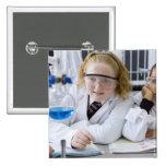 Dos chicas en capas del laboratorio del uniforme pin cuadrado