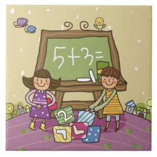Dos chicas que se colocan delante de una pizarra azulejo cuadrado grande