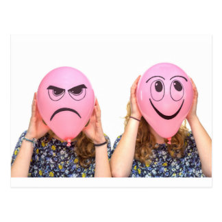 Dos chicas que sostienen los globos rosados con postal
