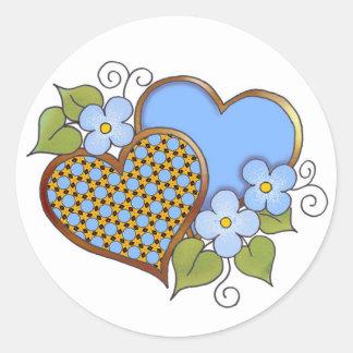 Dos corazones con los flores azules etiqueta redonda