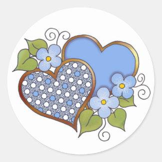 Dos corazones con los flores etiquetas redondas