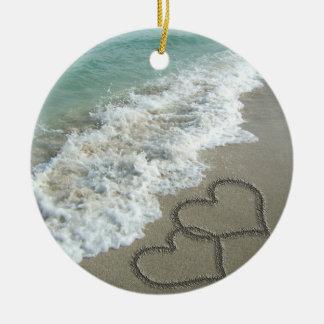 Dos corazones de la arena en la playa adorno navideño redondo de cerámica