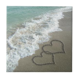 Dos corazones de la arena en la playa, océano romá azulejo cuadrado pequeño