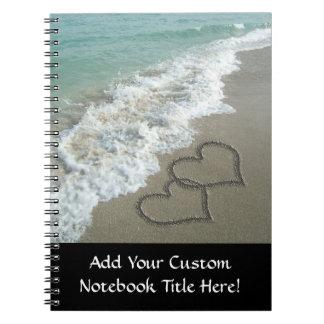 Dos corazones de la arena en la playa, océano romá cuaderno