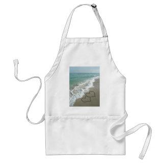Dos corazones de la arena en la playa, océano romá delantal